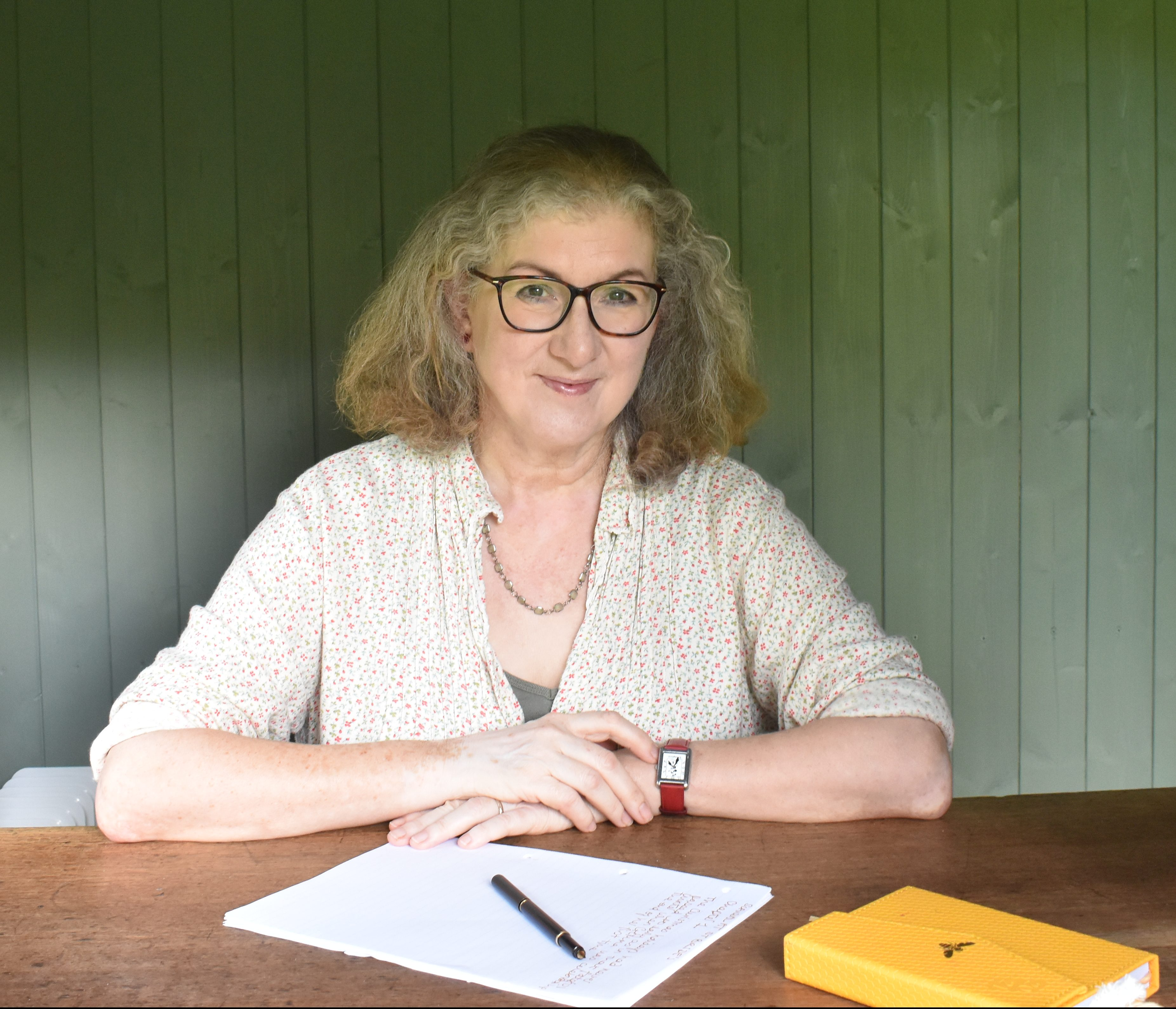 Photo of the author at work in her writing hut